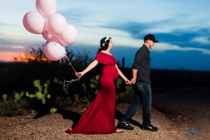pink balloons red maternity dress walking through desert