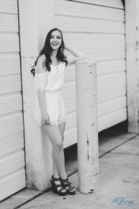 crossed legs pose white dress senior portrait