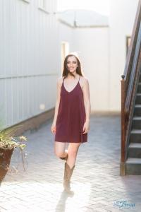 cowboy boots burgundy dress walking senior portrait pose