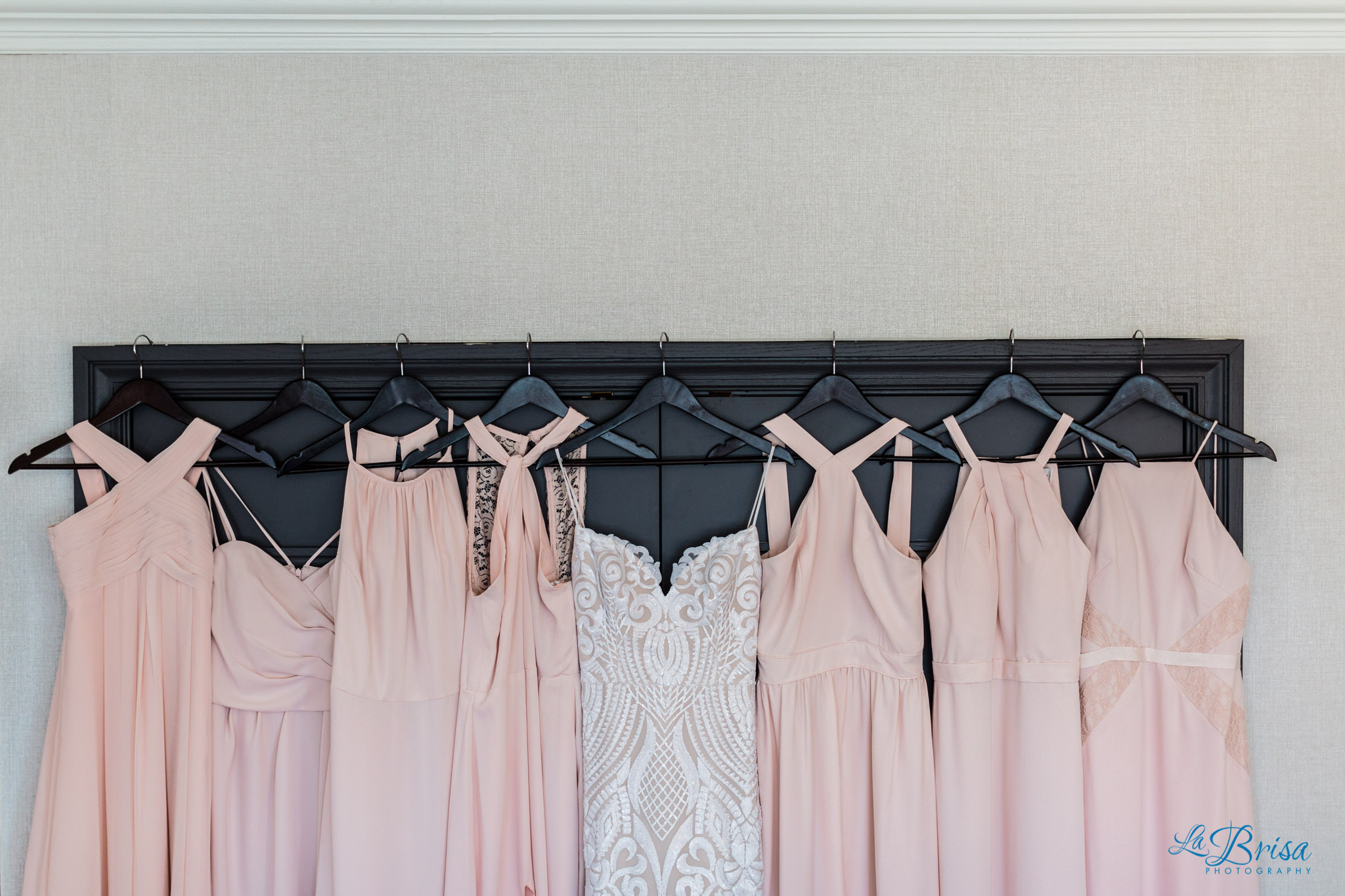 wedding gown hung next to peach bridesmaids dresses